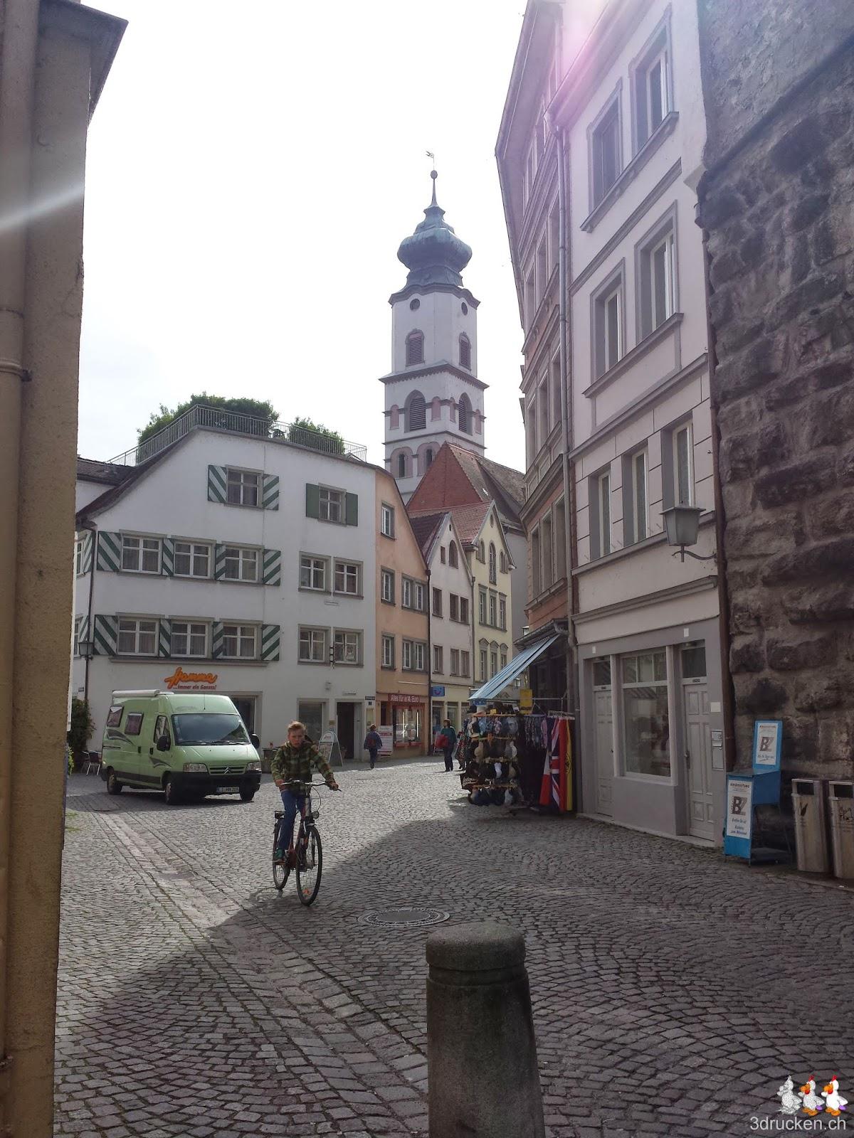 Foto in eine Gasse mit dem typischen Kopfsteinpflaster, im Hintergrund ein Kirchturm