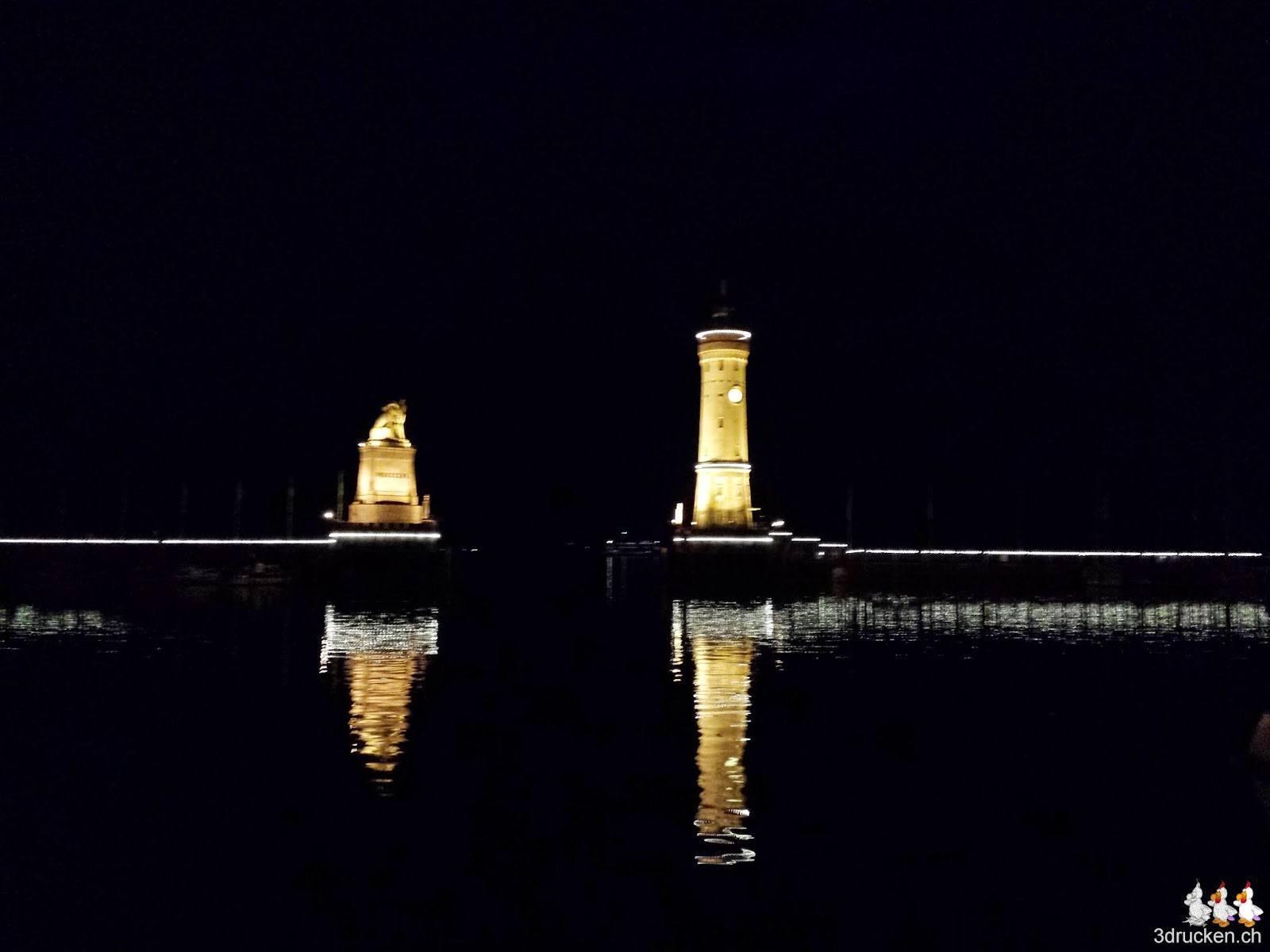 Foto der beleuchteten Hafeneinfahrt von Lindau bei Nacht mit Leuchtturm und Löwen