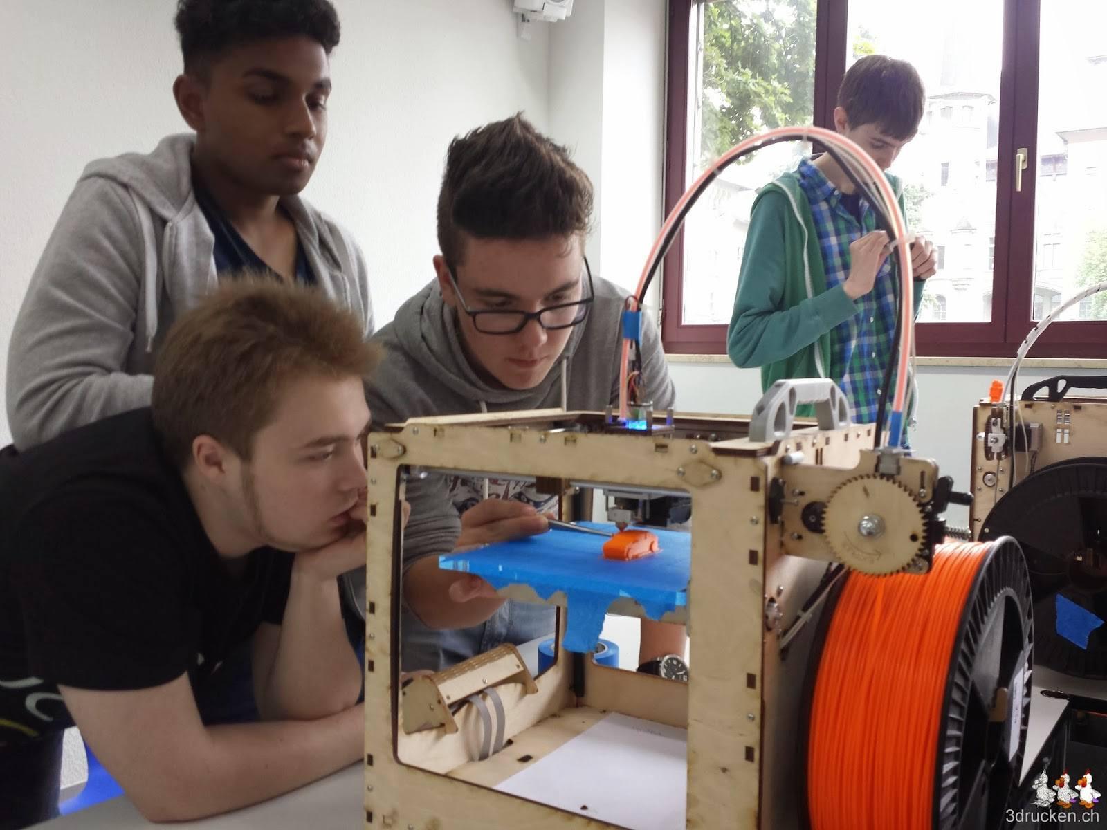 Foto einer Gruppe Lernenden, welche den Ultimaker Original bei der Arbeit beobachtet und versucht beim Drucken zu helfen