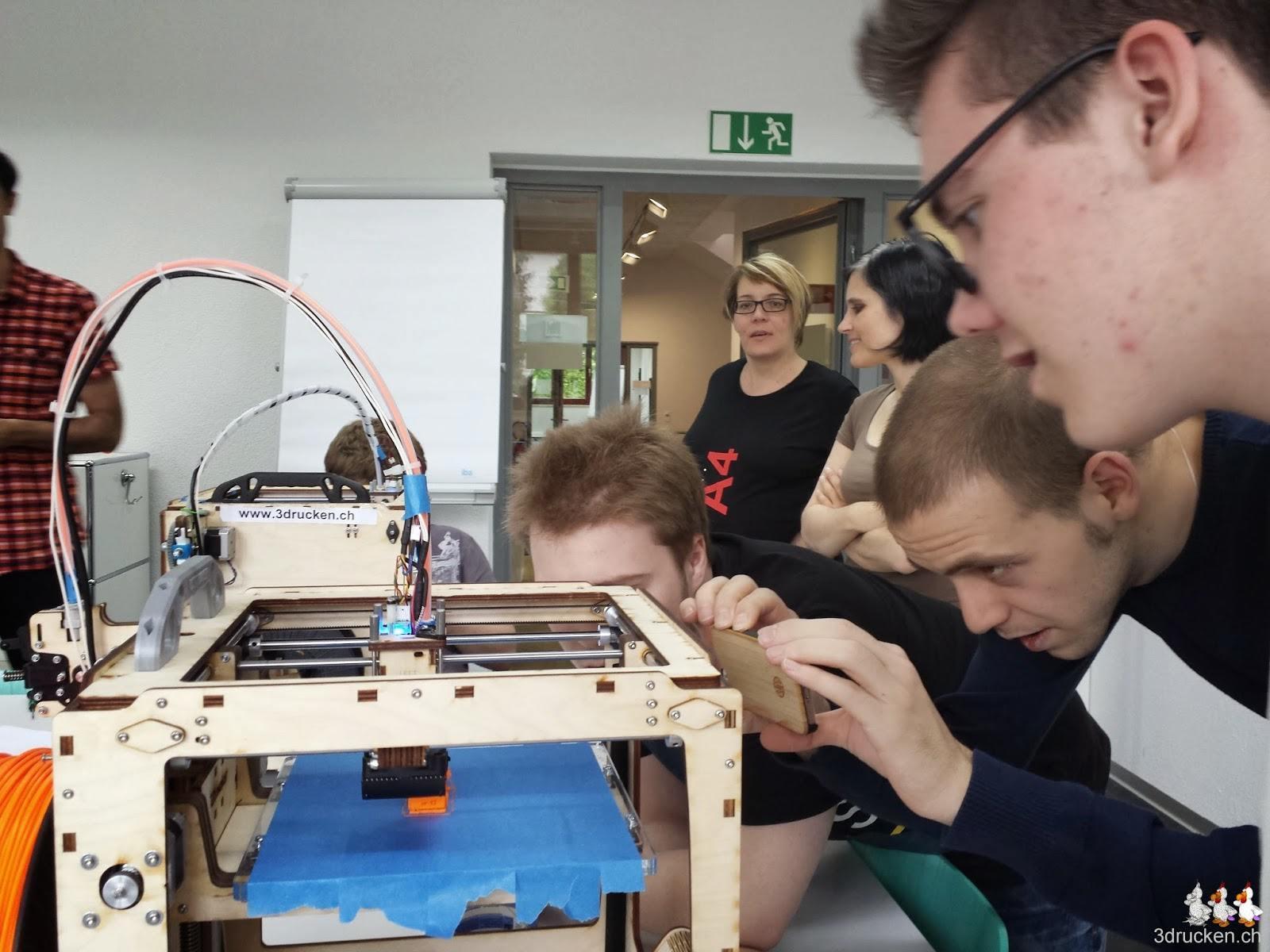 Foto einer Gruppe Lernenden mit Begleiter welche einen Druck am Ultimaker Original mit dem Handy filmen