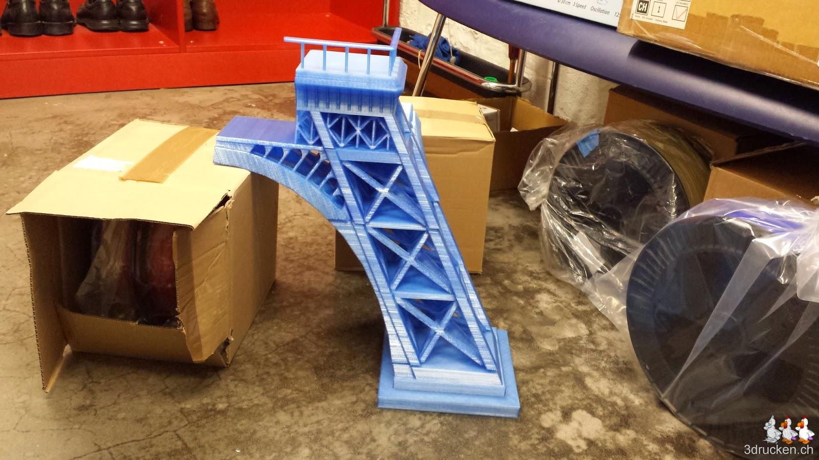 Foto eines provisorisch mit Kartons abgestützten Beins des Eiffelturms