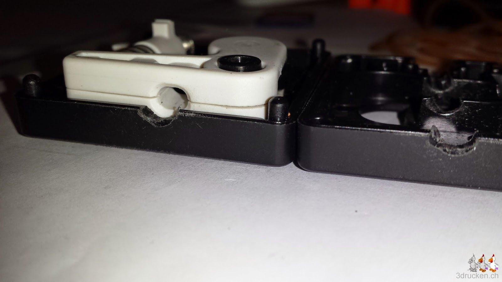 Foto der Unterseite des Feedergehäuses des Ultimaker 2 mit deutlich erkennbarem Abrieb an der Öffnung durch schräg eingezogenes Filament