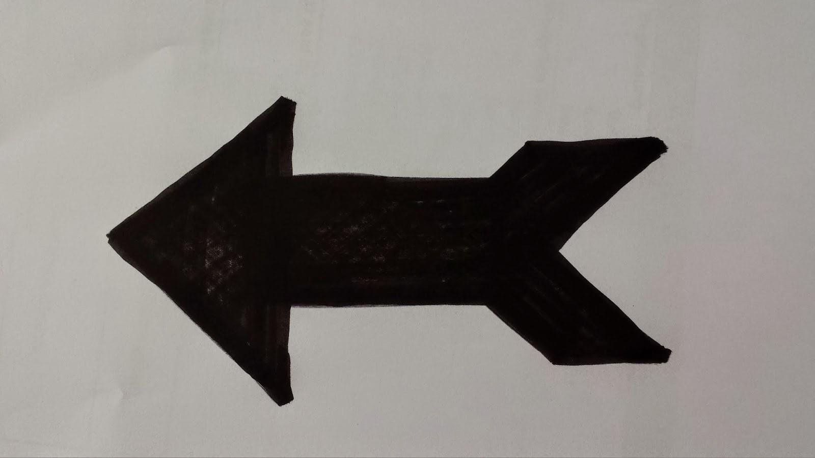 Foto einer mit schwarzem Filzstift gezeichneten Form eines Pfeils auf einem weissen Blatt Papier