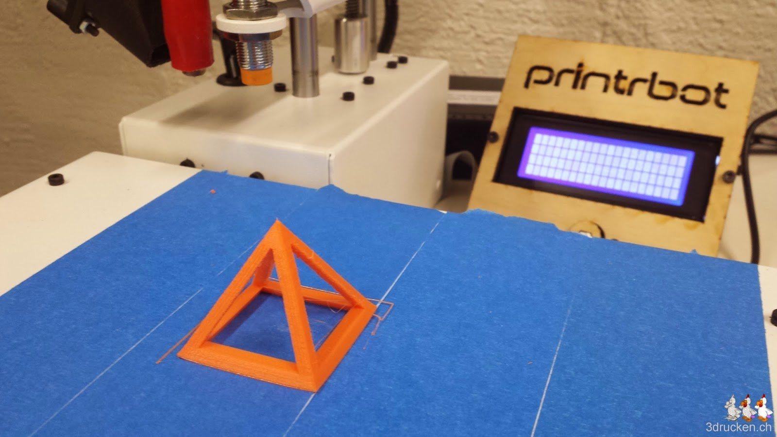 Foto des Drucktischs des Printrbot Simple Metal mit oranger Testpyramide darauf mit dem LCD mit schlechtem Betrachtungswinkel im Hintergrund