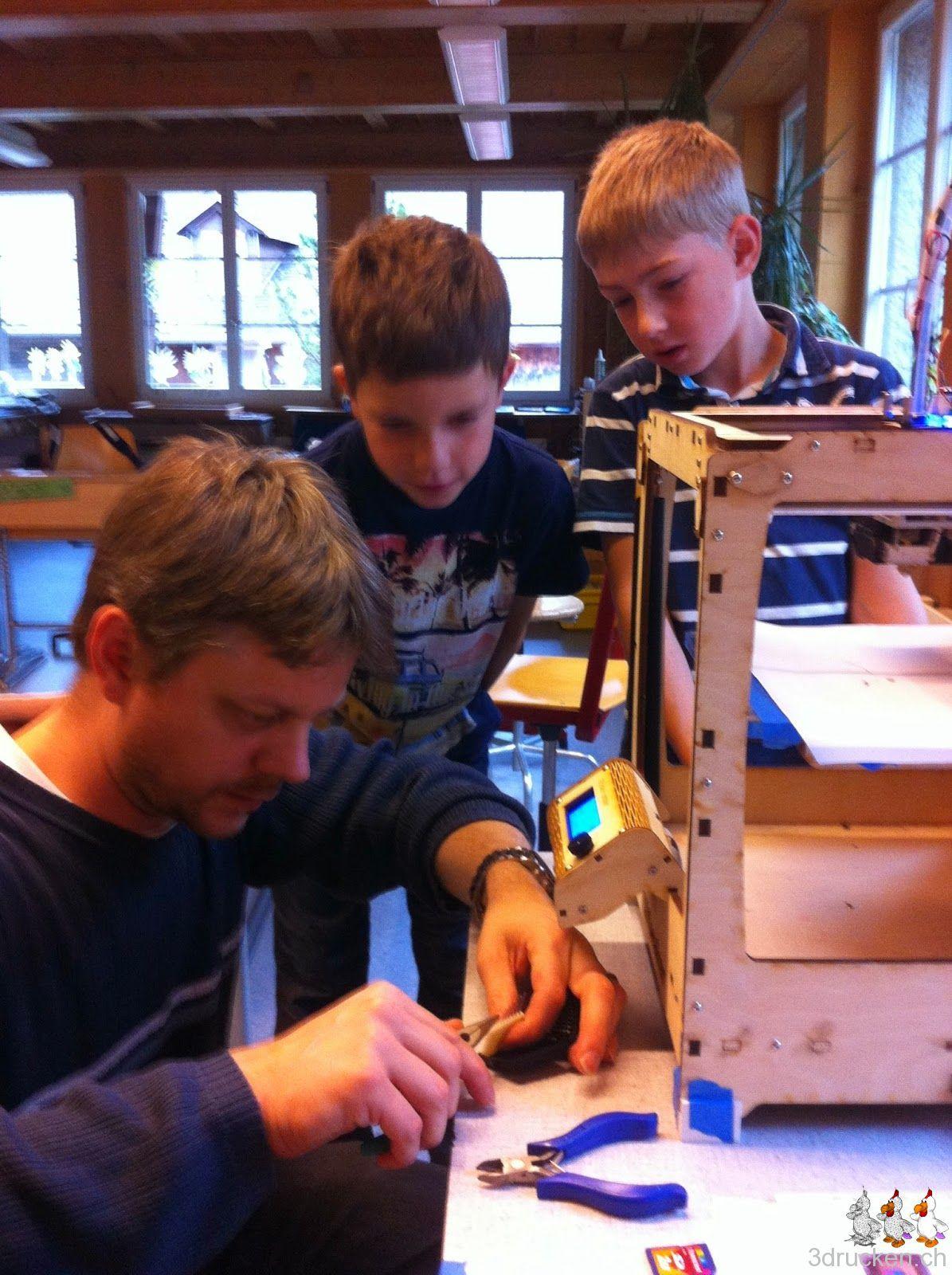 Foto von Gregor bei der Arbeit mit zwei Schülern als neugierige Zuschauer