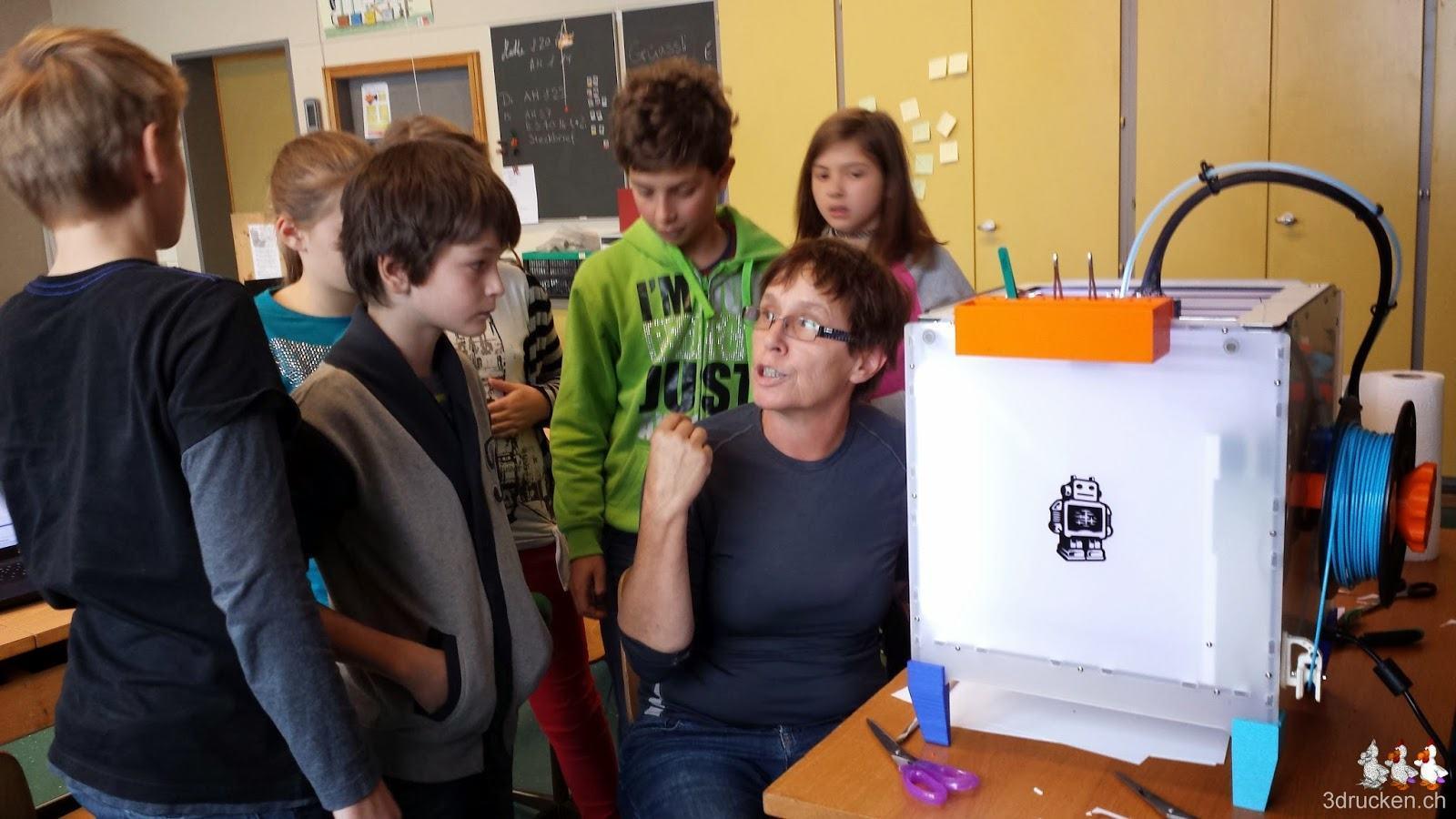 Foto einer Gruppe Schülerinnen und Schüler mit Uorschla am 3D-Drucker Ultimaker 2