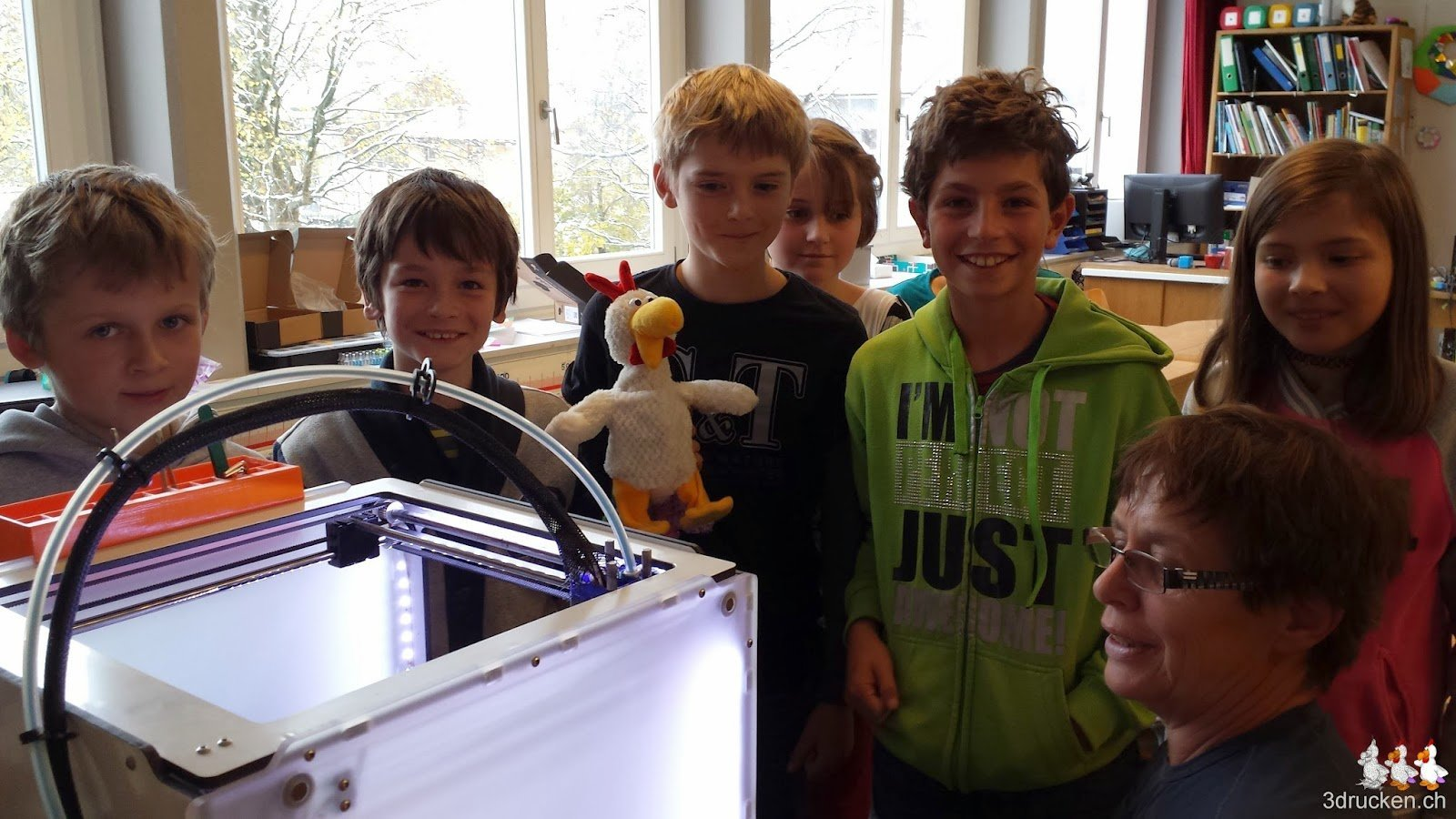 Gruppenbild am 3D-Drucker mit den Schülerinnen und Schülern, Uorschla und dem Güggel