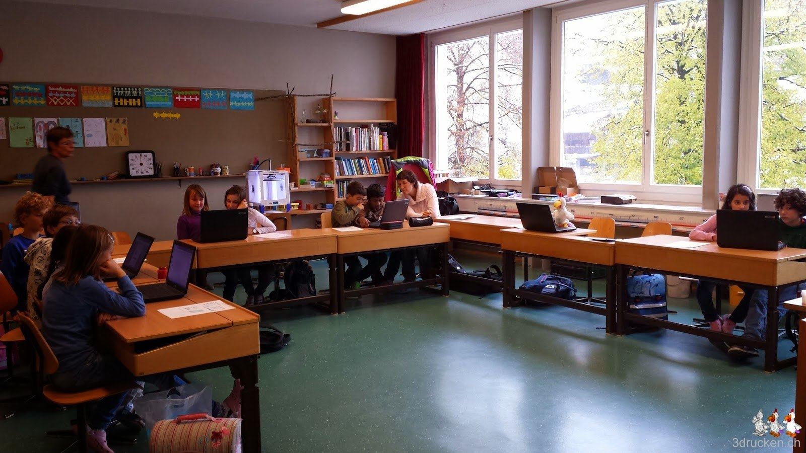 Foto des Klassenzimmers mit fleissig arbeitenden Schülerinnen und Schülern