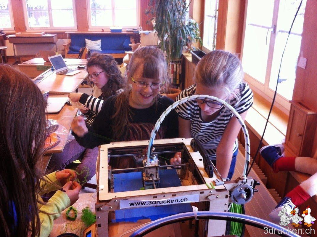 Schülerinnen schauen dem 3D-Drucker bei der Arbeit zu