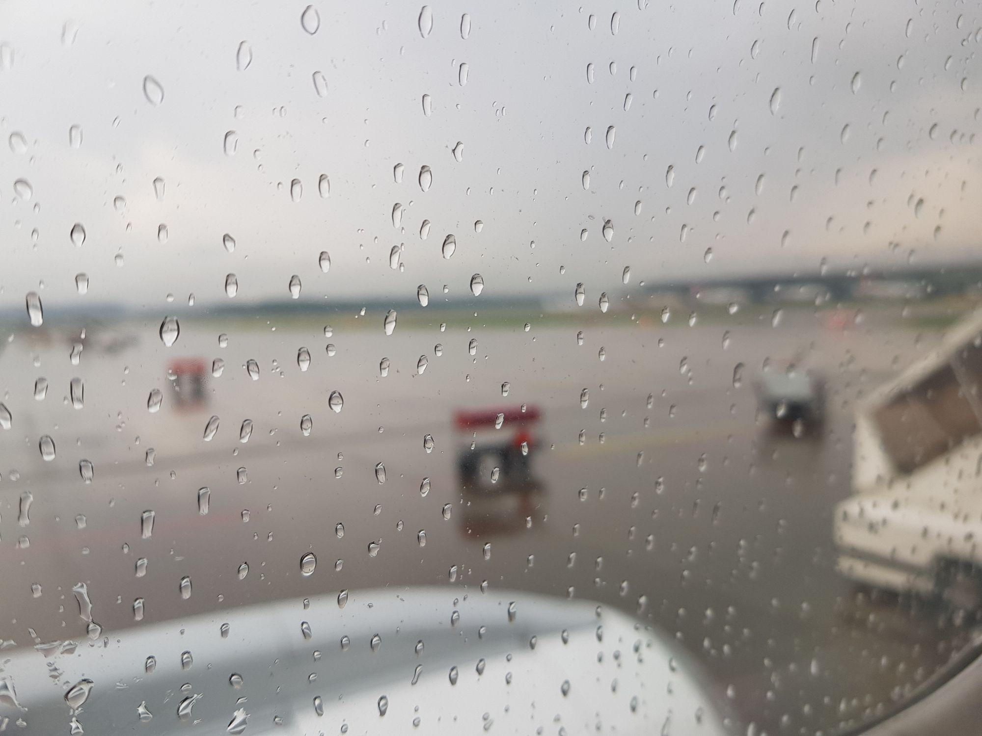 Regentropfen an der Scheibe des Flugzeugs in Zürich.
