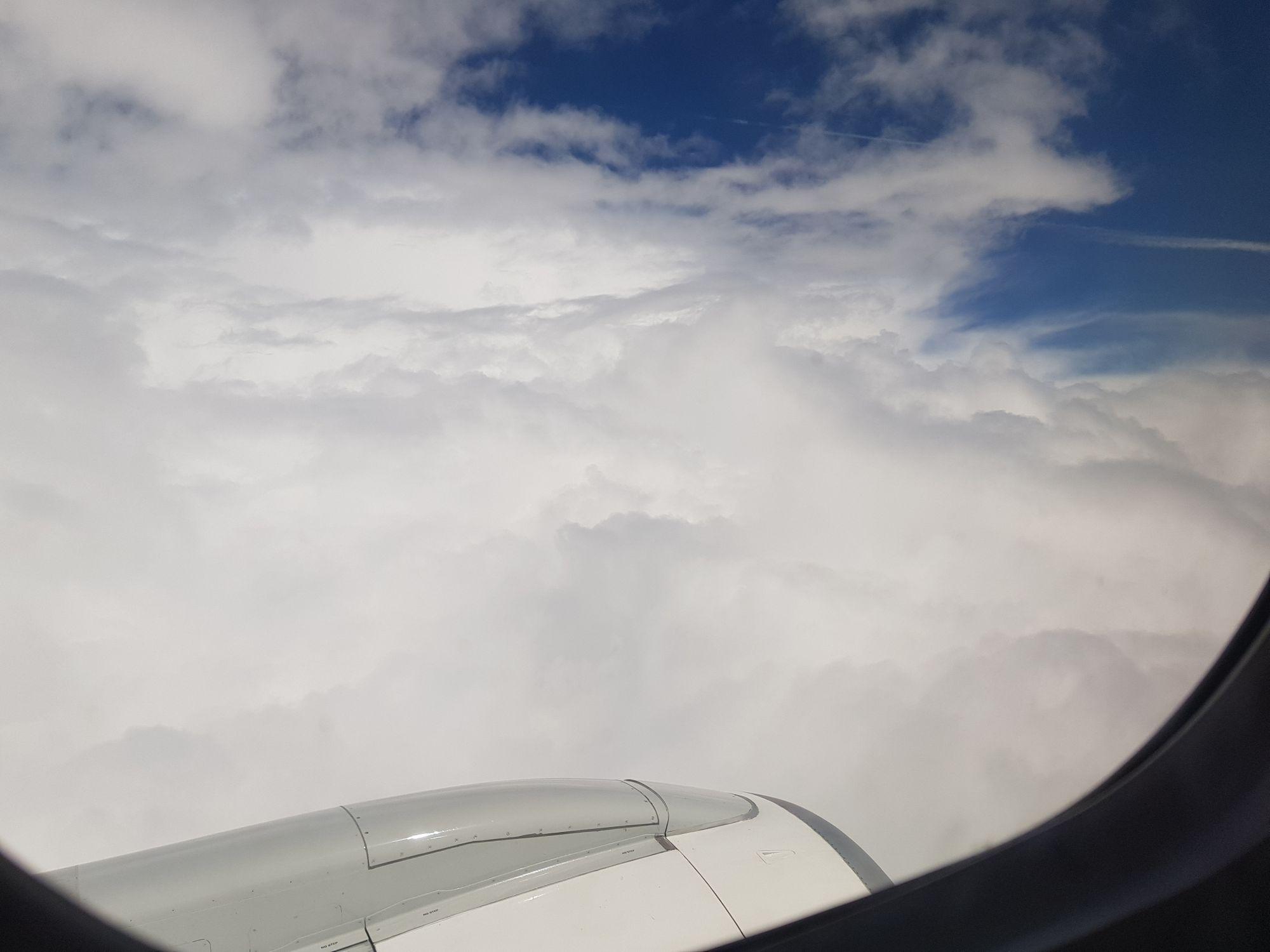 Wolken und das Triebwerk des Flugzeugs aus dem Fenster fotografiert.