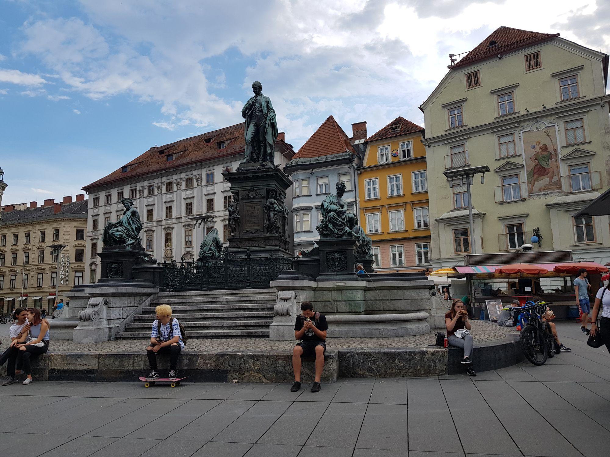 Erzherzog-Johann-Brunnendenkmal mit Leuten die auf der untersten Stufe sitzen.