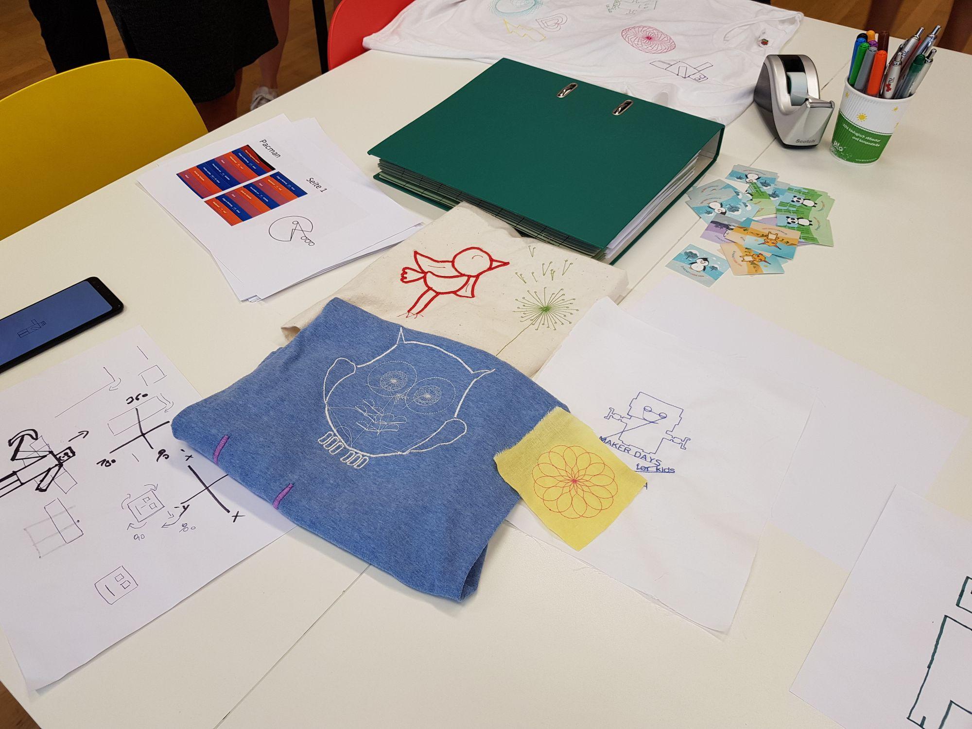 Ausgewählte Stickereiarbeiten und Skizzen auf dem Tisch.