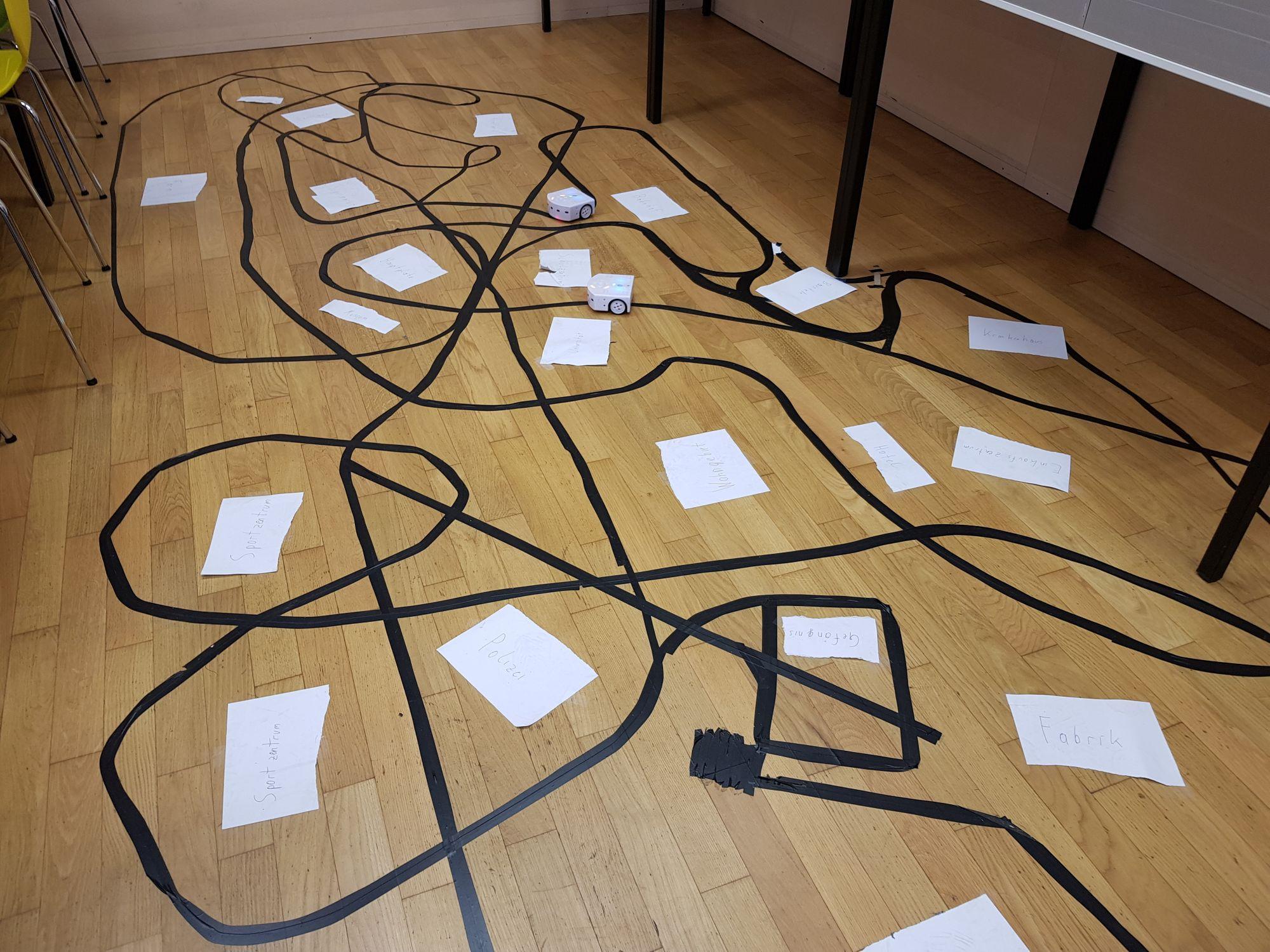 Mittels schwarzem Band geklebte Linien auf dem Boden, denen die Roboter folgen.