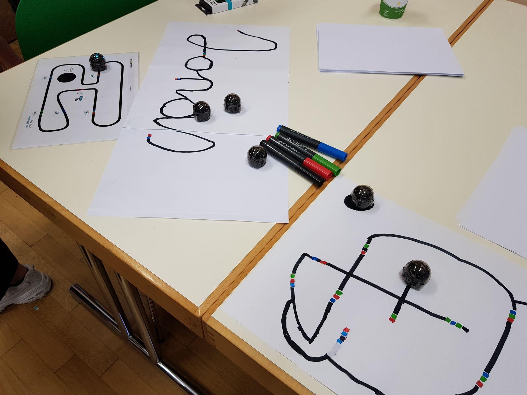 Schwarze Linien und Farbcodes, denen die Ozobot Roboter folgen.
